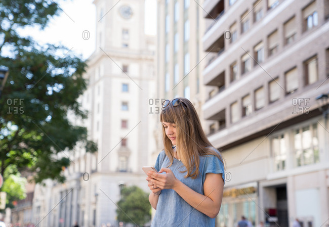 Blonde young cheerful female with sunglasses in blue T-shirt standing on street of big city and typing message on smartphone