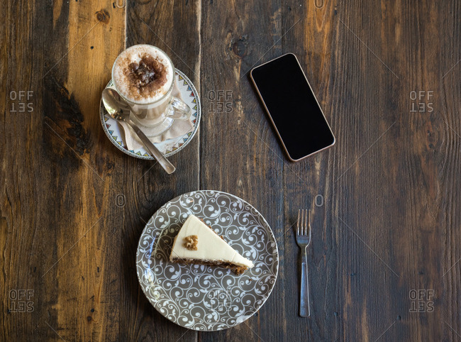 Cup of coffee, slice of cake, and phone on a table