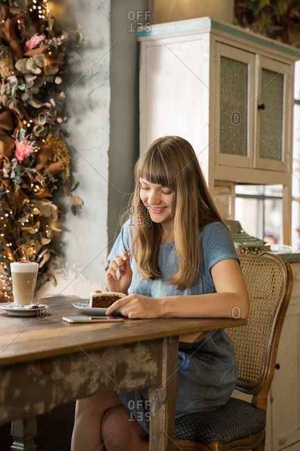 Blonde happy young female with bangs in casual blue T-shirt smiling and using a phone while holding cup of coffee in cozy cafe