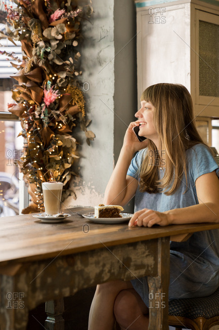 Blonde happy young female with bangs in casual blue T-shirt smiling and talking on smartphone while holding cup of coffee in cozy cafe