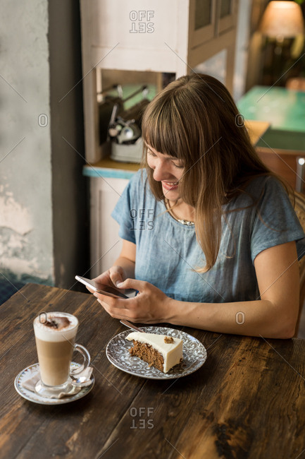 Blonde young cheerful female in casual clothes typing message on smartphone while sitting at table with coffee and dessert in cozy cafe