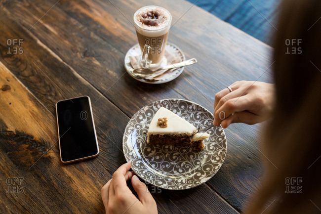 Female holding fork and sitting at table with blank screen smartphone next to coffee and cake on plate with ornament