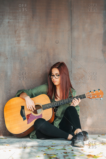 Stylish content woman thoughtfully playing guitar sitting on ground with crossed legs