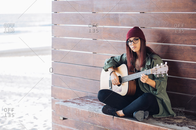 Stylish content woman thoughtfully playing guitar sitting on ground with crossed legs and looking at camera