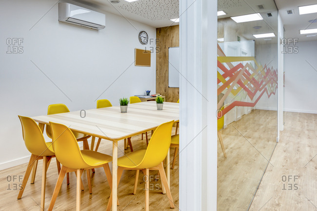 Light corridor with wooden floor among glass walls of light modern cozy office conference zones with comfortable yellow chairs at big wooden tables
