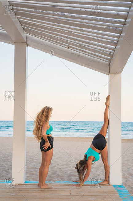 Inspired women doing a handstand on beach