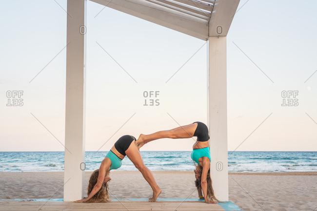 Sportive women doing acrobatic yoga posture double dog down on sandy beach