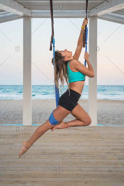 Cheerful woman stretching leg on blue hammock for aerial yoga on wooden stage