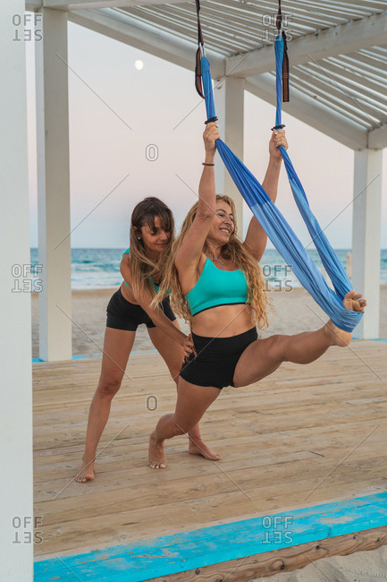 Careful woman supporting girl friend making acrobatic yoga exercise hanging on hammock on wooden stand at beach