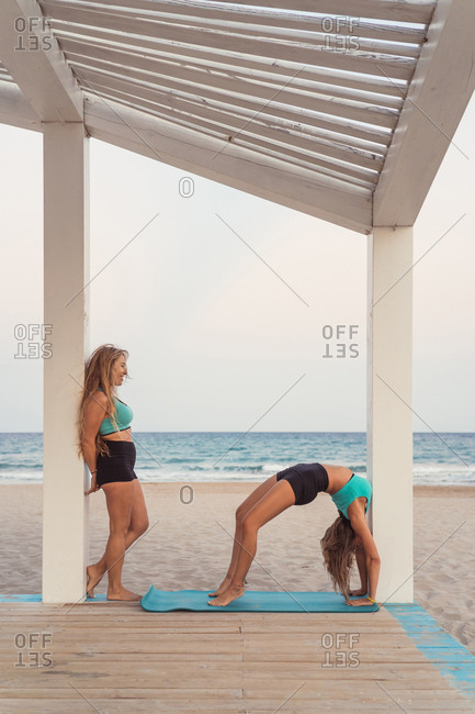 Partner looking at woman making bridge in acrobatic yoga on background of ocean