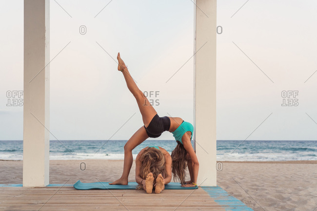Flexible woman making bridge in acrobatic yoga on background of ocean