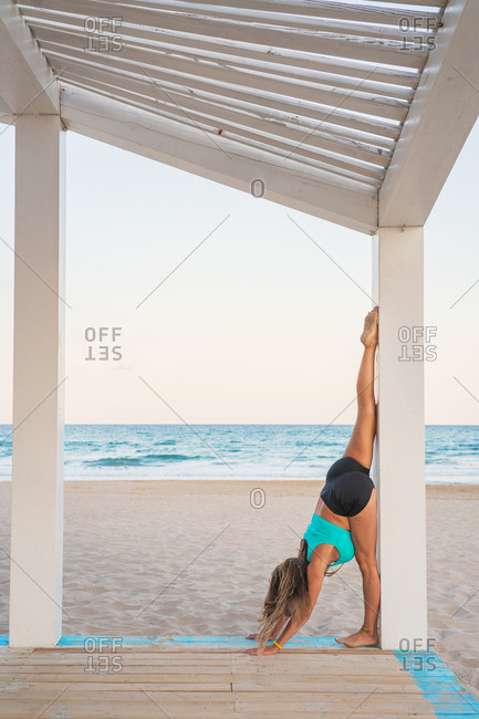 Side view of sportive power woman standing upside down on raising leg up on wooden stand on beach