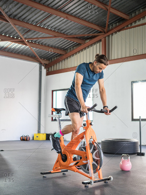 Sportsman exercising on stationary bicycle in light modern gym