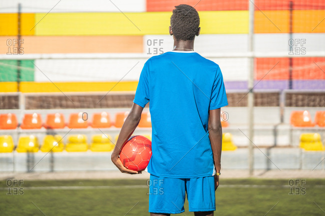 Back view of black guy in blue sportswear carrying red ball while standing against stadium seats on football field