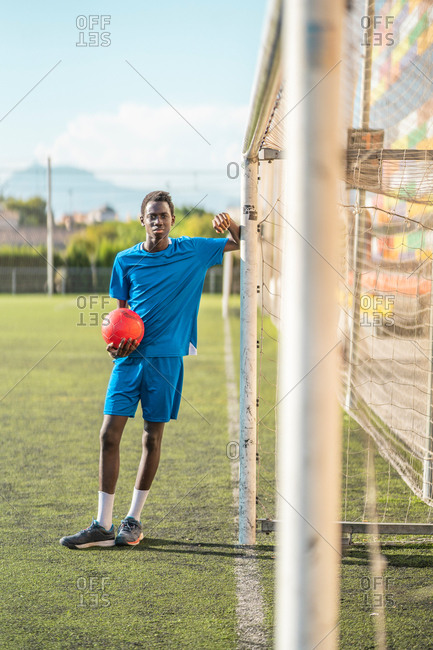 Full body African American teenager in sportswear holding ball and leaning on net during training on football field