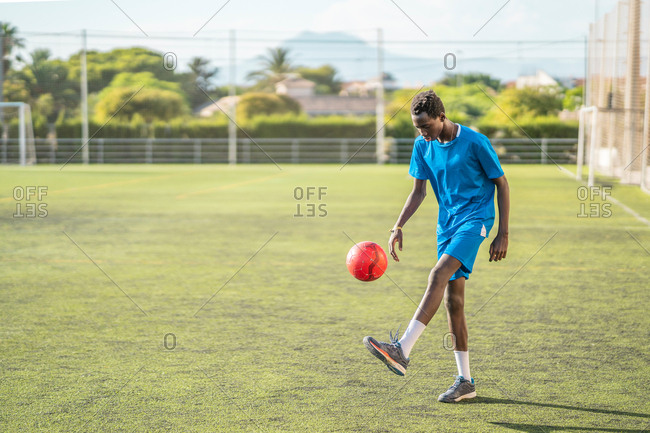 Ethnic teenager juggling football ball
