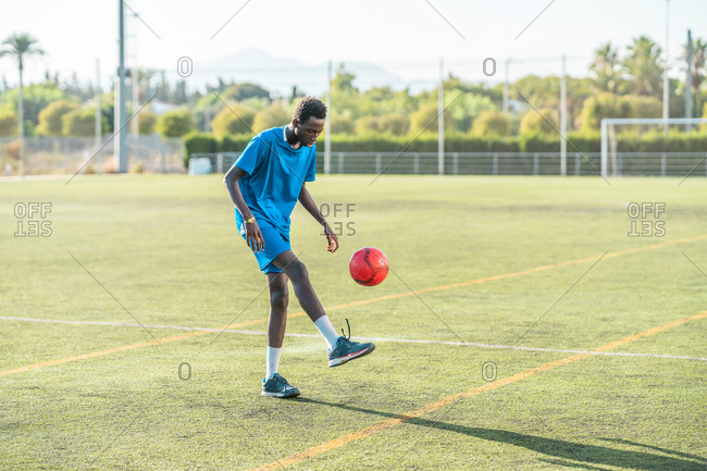 Ethnic teenager juggling football ball