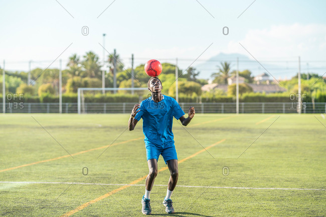 Skinny black teenager jugging football ball on head