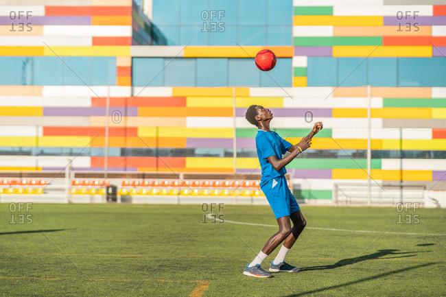 Skinny black teenager jugging football ball on head