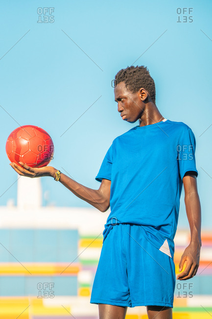 Black teenager with football ball against sky