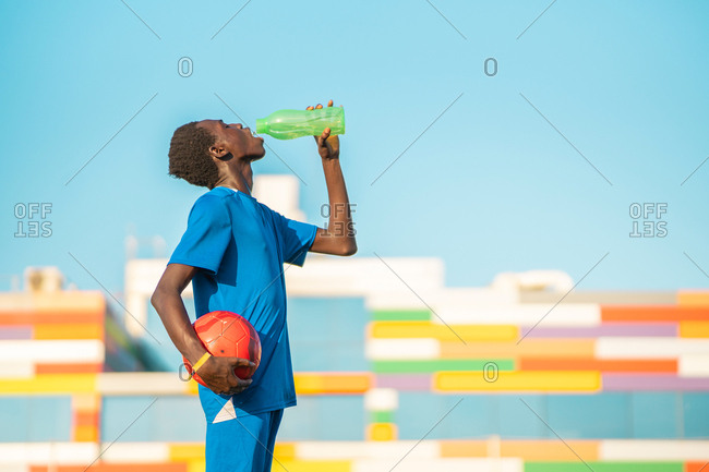 Black football player drinking water