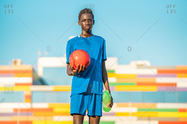 Black teenager with football ball looking at camera