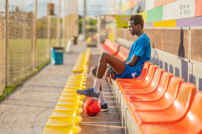 Side view of ethnic teenager with ball sitting on stadium seat and relaxing during football workout on sunny day