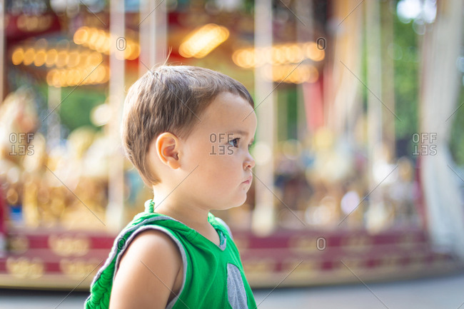 Child looking away against moving carousel at fair