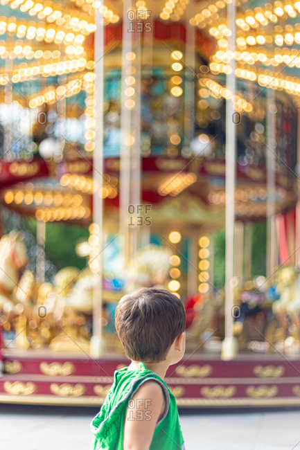 Back view of little kid in green casual clothes looking away and contemplating while standing alone against colorful rotating merry go round in amusement park during daytime