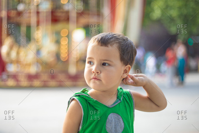 Child standing near moving carousel and dreaming at fair
