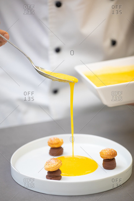 Crop cooker in uniform holding bowl and pouring yellow syrup from spoon into white plate with chocolate pastries in form of mushrooms