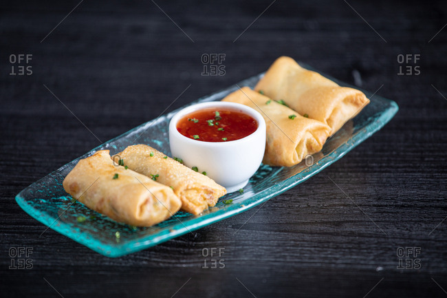 Egg rolls and dipping sauce on a clear plate