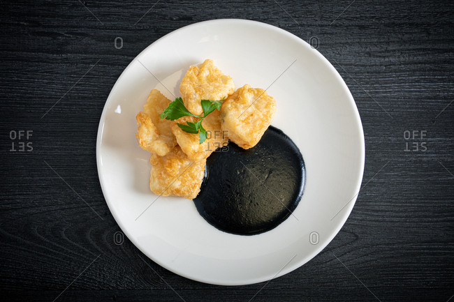 Hake breaded with squid cream in plate
