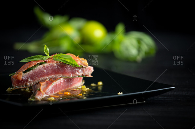 Fragrant juicy Bluefin tuna with basil ham and chicken demiglace on black plate