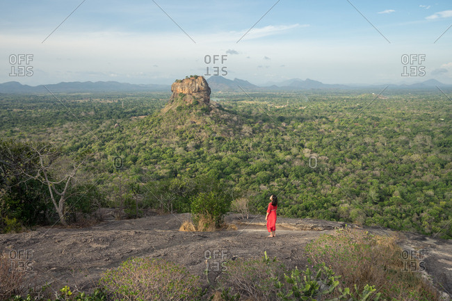 Back view of adult woman in red dress enjoying amazing view in Sri Lanka