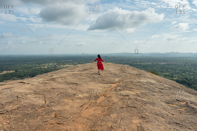 Back view of unrecognizable woman in red dress enjoying amazing view  in Sri Lanka