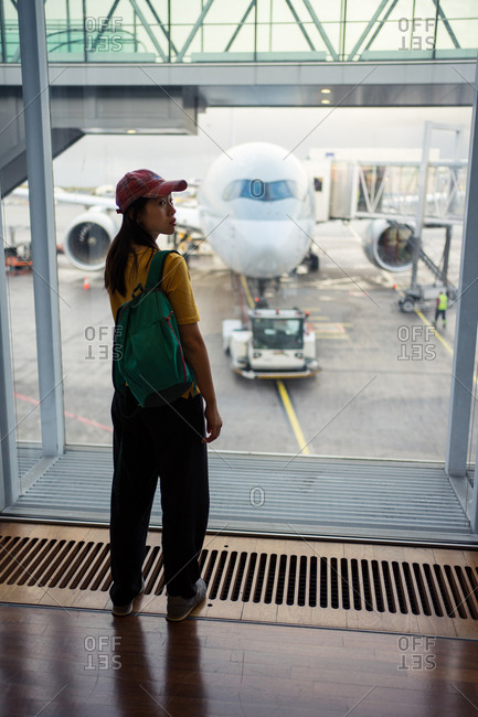 Back view of woman in cap, backpack and sportive wear waiting at airport