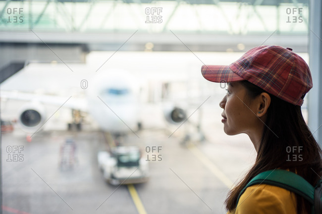 Side view of Asian woman in cap at window with view of runway with plane and car loader