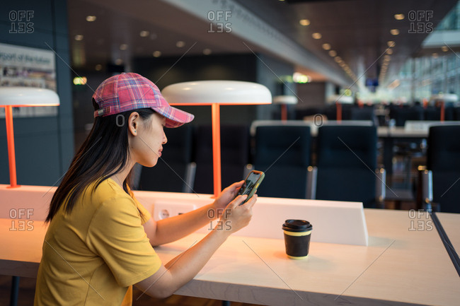 Side view of Asian woman in cap surfing mobile phone and drinking coffee from disposable cap at table before schedule board in airport