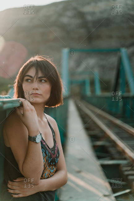 Thoughtful young woman looking away holding iron fence handrail in railway bridge in sunny day