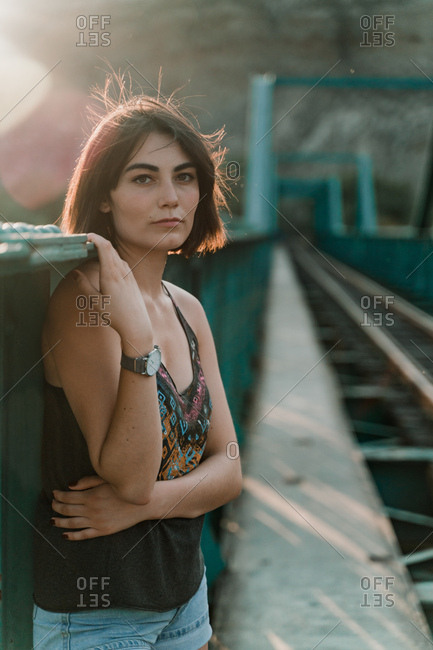 Thoughtful young woman looking at camera holding iron fence handrail in railway bridge in sunny day
