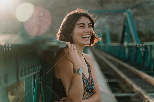 Cheerful young woman looking away with laugh holding iron fence handrail in sunny day on railway bridge