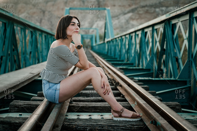 Side view of pensive stylish woman with hairstyle sitting on hand placing at railway leading to distance along ornamental fence