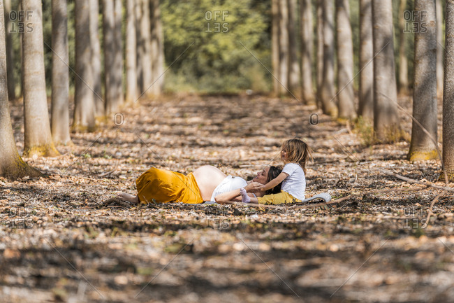 Pregnant mother and little daughter resting in park
