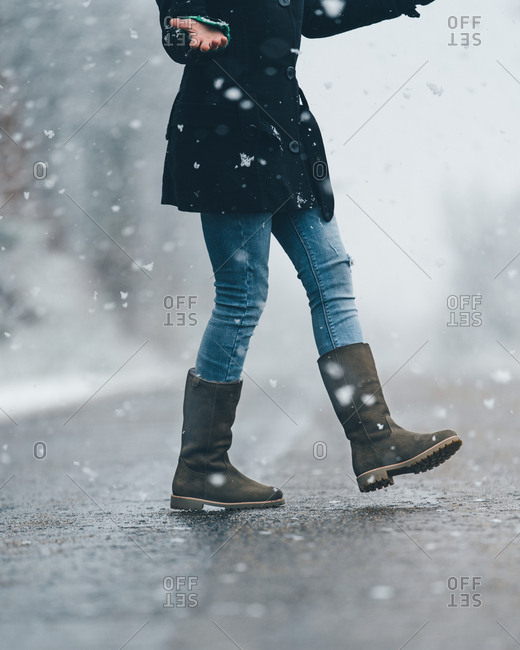 Side view of lonely female in black jacket and jeans crossing empty country road on snow and gloomy winter day