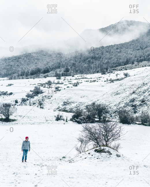 Casual man in red knitted cap wearing striped sweater and jeans walking on winter field with hills covered with snow
