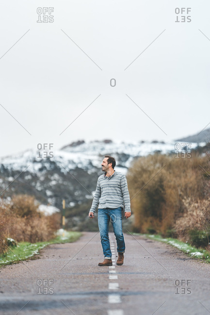 Adult male in stripped jumper and jeans walking on country roadway with hills covered by snow on background on gloomy cloudy day