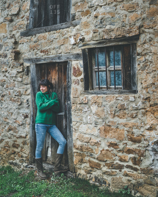 Casual female in green sweater and jeans standing with crossed arms next to door of old stone country house and feeling cold on gloomy damp autumn day