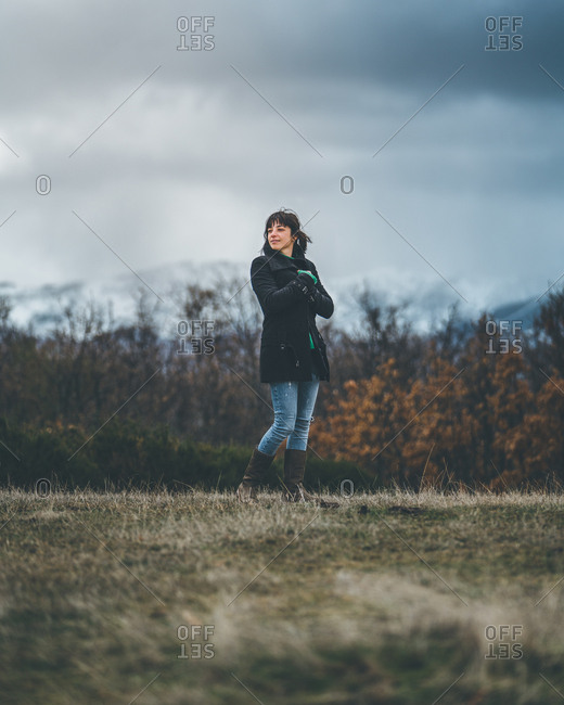 From below of pretty casual female in black coat and jeans standing with crossed arms and feeling cold on autumn field with hills covered by snow and grey sky with dark clouds on background