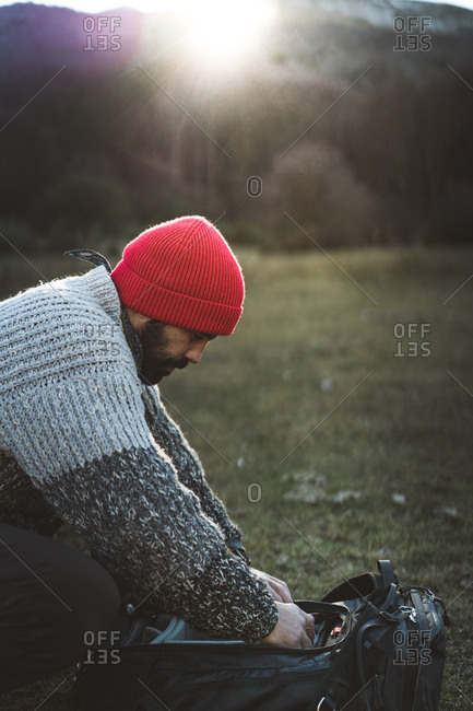Side view of bearded male photographer in red knitted cap and grey sweater grabbing a professional camera in a backpack while in mountains